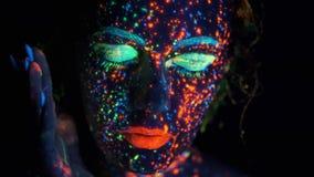 Peinture de lueur sur le visage de la fille Portrait de plan rapproché d'une belle jeune femme avec la peinture rougeoyante sur s banque de vidéos