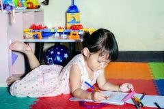 Peinture de petit enfant avec les crayons colorés à l'intérieur à la maison Image libre de droits