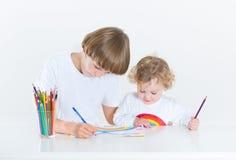 Gar on avec la peinture de fille au bureau de salle de classe photo stock i - Peinture petit blanc ...
