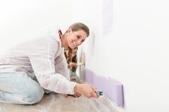 Peinture de sourire de femme avec le rouleau sur le mur image stock