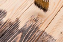 Peinture du bois, main tenant une brosse Images libres de droits