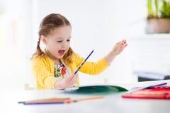 Peinture et écriture de petite fille Photographie stock libre de droits