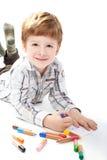 Peinture mignonne de garçon sur un livre blanc Photographie stock