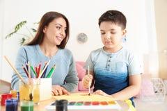 Peinture mignonne de petit enfant à la table avec la jeune mère Photos stock