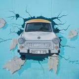 Peinture murale de voiture de Trabant traversant Berlin Wall au SI est photo stock