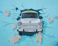 Peinture murale de voiture de Trabant traversant Berlin Wall au SI est photos stock
