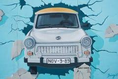 Peinture murale de voiture de Trabant traversant Berlin Wall au SI est image stock