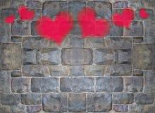 Peinture rouge et rose de coeur sur le mur de briques en pierre Photo stock