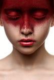 Peinture rouge sur le visage de la fille de beauté Photographie stock libre de droits