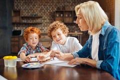 Peinture supérieure consciente de dame avec des petits-enfants à la maison Photos libres de droits