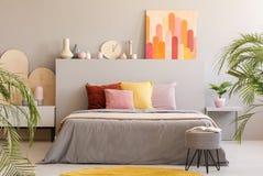 Peinture sur la tête de lit grise du lit avec les coussins colorés dans le bedr photos libres de droits