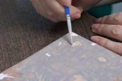Peinture sur la toile par des nombres Une femme tient une brosse et la dessine photo libre de droits