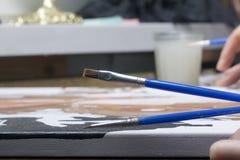 Peinture sur la toile par des nombres Une femme tient une brosse et la dessine Récipients numérotés avec des peintures et brosses images libres de droits