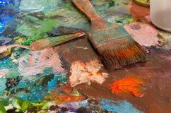 Peintures à l'huile et brosse sur la palette abrégez le fond images libres de droits