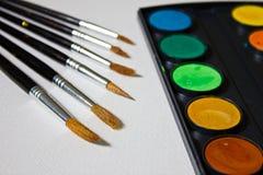Peintures, brosses et album avec le papier d'aquarelle Images libres de droits