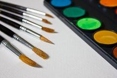 Peintures, brosses et album avec le papier d'aquarelle Photo stock