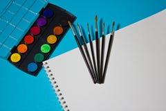 Peintures, brosses et aquarelles pour l'album sur un fond bleu Photographie stock