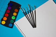 Peintures, brosses et aquarelles pour l'album sur un fond bleu Photo libre de droits