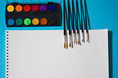 Peintures, brosses et aquarelles pour l'album sur un fond bleu Photos libres de droits