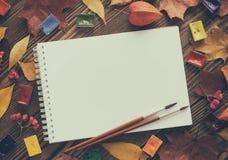 Peintures d'aquarelle, brosses pour peindre et feuille de livre blanc Photographie stock libre de droits