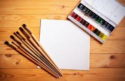 Peintures d'aquarelle, brosses pour peindre et feuille de papier sur le fond en bois Image libre de droits