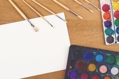 Peintures d'aquarelle, brosses pour peindre et feuille vide de livre blanc sur le fond en bois Images stock