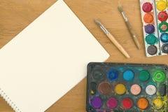 Peintures d'aquarelle, brosses pour peindre et feuille vide de livre blanc sur le fond en bois Images libres de droits