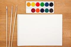 Peintures d'aquarelle, brosses pour peindre et feuille vide de livre blanc sur le fond en bois Vue supérieure Photos stock