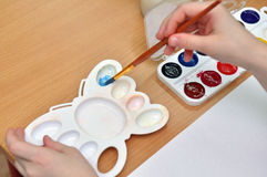Peintures d'aquarelle de mélange d'enfant sur une palette Photo stock