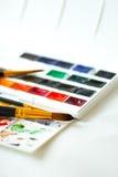 Peintures d'aquarelle réglées, palette et brosses Images stock