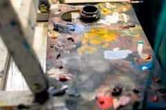 Peintures de différentes couleurs sur une palette multicolore des peintures à l'huile mélangées illustration libre de droits