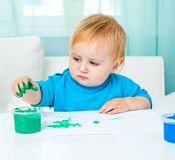 Peintures de doigt d'aspiration de petite fille Image stock