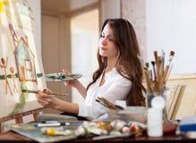 Peintures de femme sur la toile dans l'atelier Photographie stock