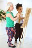 Peintures de fille et de garçon sur un chevalet Photo libre de droits