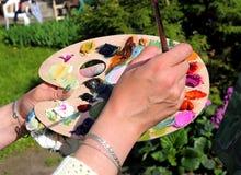 Peintures de mélange dans la palette ovale Photographie stock libre de droits