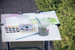 Peintures et une brosse dans un verre image stock
