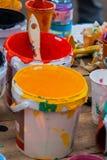 Peintures multicolores dans des pots et la brosse sur la table, chaos créatif Photographie stock libre de droits