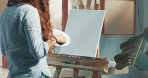 Peintures rousses mignonnes de fille dans son studio image libre de droits