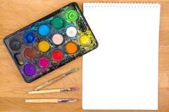 Peintures utilisées d'aquarelle, brosses pour peindre et feuille vide de livre blanc sur le fond en bois Vue supérieure Photographie stock