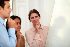 Peinzend commercieel team die op een whiteboard kijken royalty-vrije stock afbeeldingen
