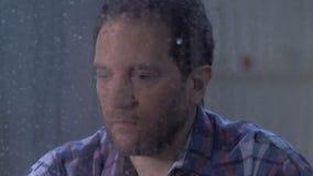 Peinzend mannelijk sluitend gezicht met palmen in wanhoop achter regenachtig venster, problemen stock video