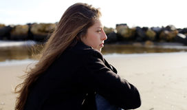 Peinzend meisje die droevig in de winter voor het strand voelen Stock Foto's
