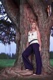 Peinzend mooi jong meisje die zich op de machtige wortels van een oude boom in het verrukte bos bevinden Stock Foto's