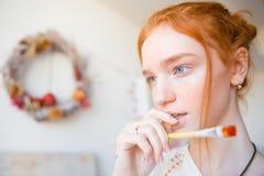 Peinzend mooi jong vrouwelijk holding penseel en het denken stock foto's