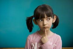 Peinzend schoolmeisjeverblijf dichtbij schoolbord. Royalty-vrije Stock Foto