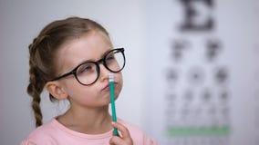 Peinzend slim meisje die glazen dragen, testend visie met ooggrafiek in kliniek stock footage