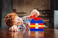Peinzend weinig jong geitje het spelen met bouwreeks stock foto's