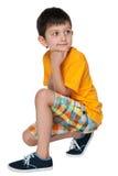 Peinzend weinig jongen in het gele overhemd Royalty-vrije Stock Afbeelding