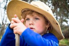 Peinzend weinig jongen met hoed het spelen met een stok in openlucht royalty-vrije stock afbeelding