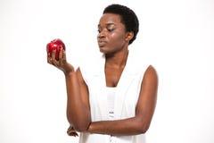 Peinzende aantrekkelijke Afrikaanse Amerikaanse jonge vrouwenholding appel en het denken royalty-vrije stock afbeeldingen